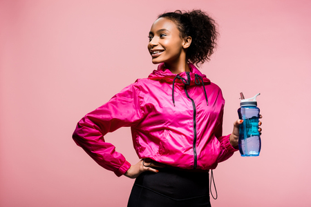 Foto de beautiful smiling african american sportswoman with sport bottle isolated on pink - Imagen libre de derechos