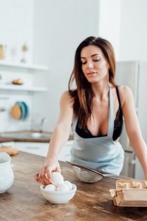 Foto per Sexy woman in underwear and blue apron holding eggs in kitchen - Immagine Royalty Free