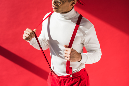Photo pour cropped view of fashionable mixed race man in suspenders posing on red - image libre de droit