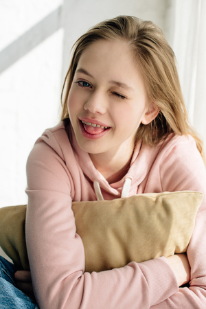 Photo pour Smiling teenage kid embracing brown cushion and looking at camera - image libre de droit