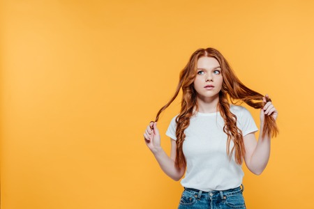 Photo pour beautiful redhead girl touching hair and looking away isolated on yellow with copy space - image libre de droit