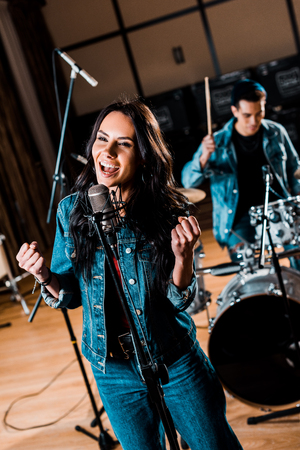 Photo for selective focus of beautiful emotional woman singing while mixed race musician playing drums in recording studio - Royalty Free Image