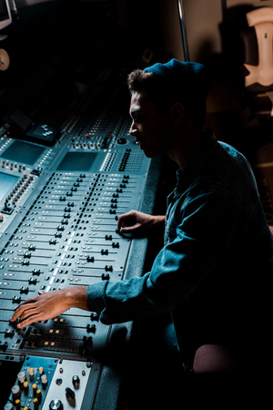Photo pour sound producer working at mixing console in dark recording studio - image libre de droit