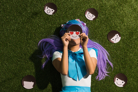 Photo pour Anime girl in purple wig lying on grass with emoticons - image libre de droit