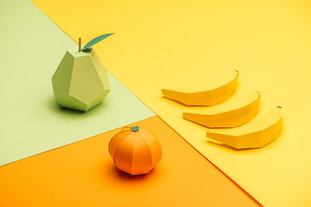 Photo pour handmade origami pear, bananas and tangerine on colorful paper - image libre de droit