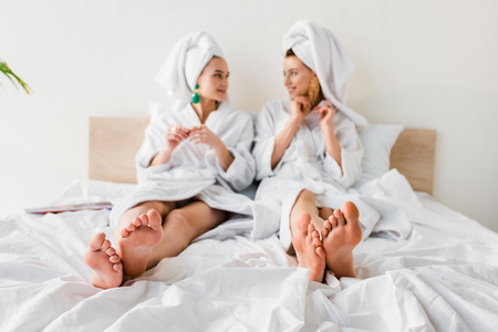 Photo for selective focus of barefoot girls in earrings, bathrobes and with towels on heads lying in bed and looking at each other - Royalty Free Image