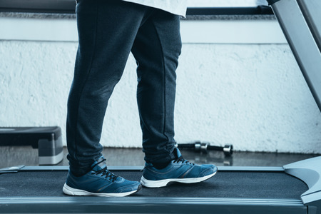 Foto per cropped view of overweight man in trainers running on treadmill at sports center - Immagine Royalty Free