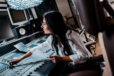 Photo pour smiling sound producer working in recording studio at mixing console - image libre de droit
