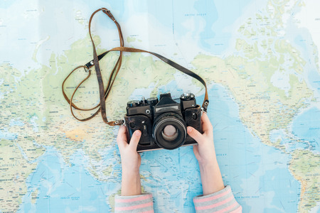 Photo pour Cropped view of child holding film camera on world map - image libre de droit