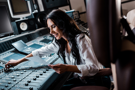 Photo pour attractive smiling sound producer working at mixing console in recording studio - image libre de droit