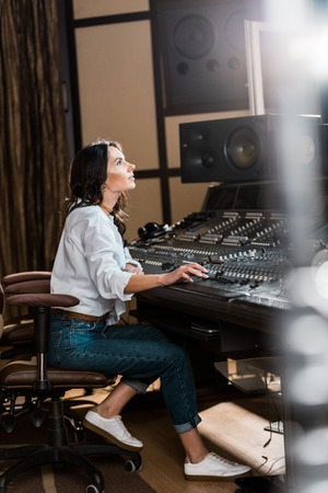 Photo pour Selective focus of attractive sound producer working at mixing console in recording studio - image libre de droit