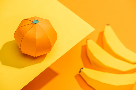 Photo pour Selective Focus of origami tangerine on yellow paper with cardboard bananas on orange background - image libre de droit