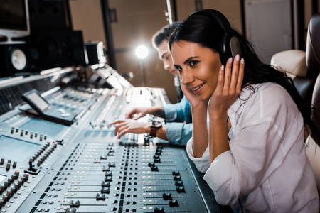 Photo pour Sound producer in headphones near mixed racial friend working at mixing console - image libre de droit