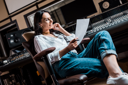 Photo pour Beautiful smiling sound producer sitting in office chair near mixing console in recording studio - image libre de droit