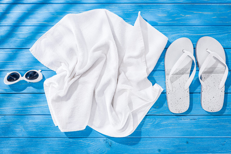 Foto de Top view of White crumpled towel, sunglasses and flip flops on blue wooden background - Imagen libre de derechos