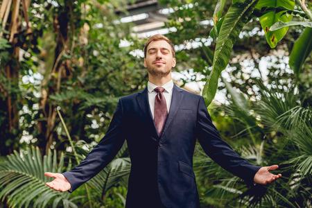 Foto de Joyful businessman with closed eyes and outstretched hands standing in greenhouse - Imagen libre de derechos