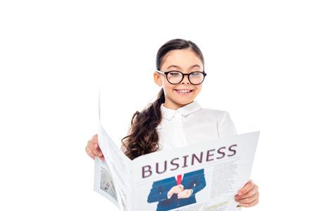 Foto de smiling schoolgirl in formal wear reading business newspaper Isolated On White - Imagen libre de derechos