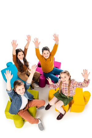 Foto de High Angle View of happy kids with outstretched hands sitting on jigsaw puzzle poufs on white - Imagen libre de derechos
