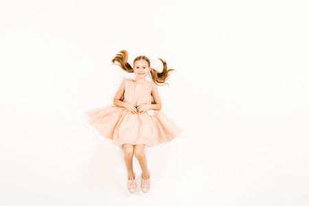 Photo for top view of happy child in pink dress looking at camera on white - Royalty Free Image