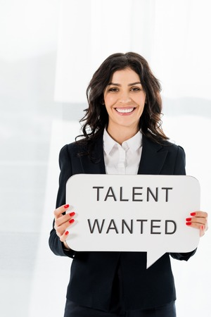 Photo for cheerful beautiful recruiter holding speech bubble with talent wanted lettering - Royalty Free Image