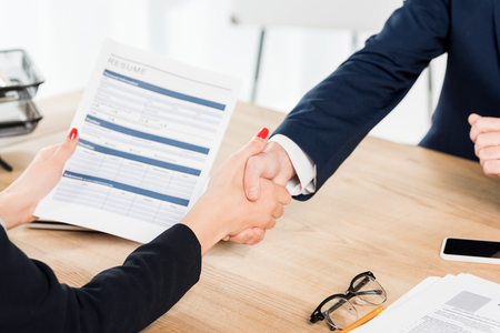 Photo for cropped view of recruiter holding resume and shaking hands with employee in office - Royalty Free Image