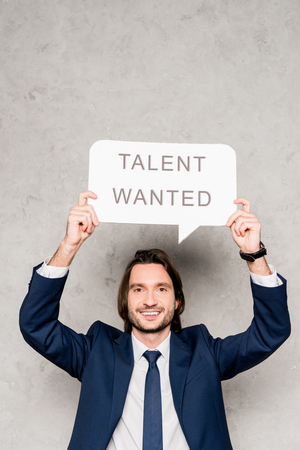 Photo for cheerful recruiter holding speech bubble with talent wanted lettering on grey - Royalty Free Image