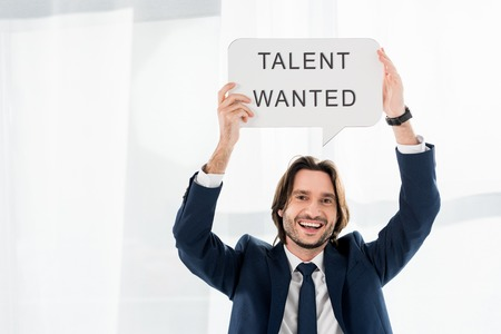 Photo for cheerful recruiter holding speech bubble with talent wanted lettering - Royalty Free Image