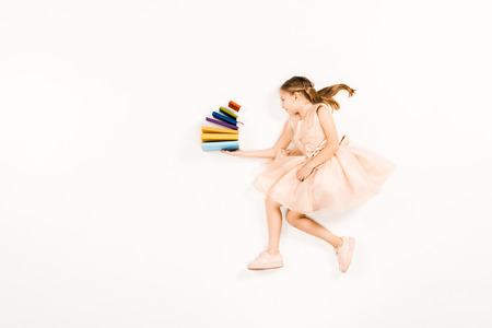 Photo for top view of cheerful kid in pink dress holding books on white - Royalty Free Image