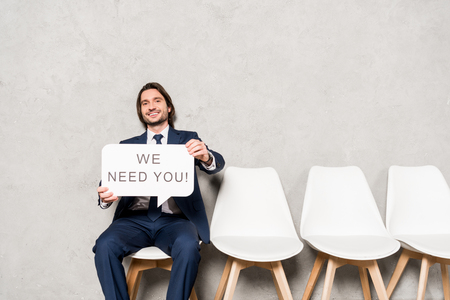 Foto de happy recruiter sitting on chair and holding speech bubble with we need you lettering - Imagen libre de derechos