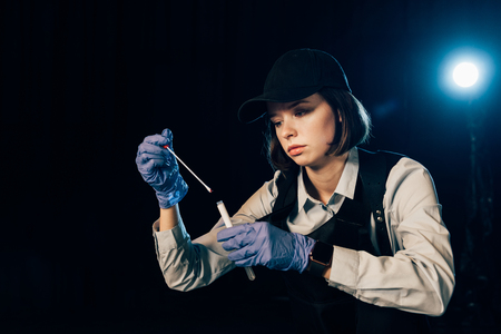Photo pour investigator in rubber gloves holding swab and test tube at crime scene - image libre de droit