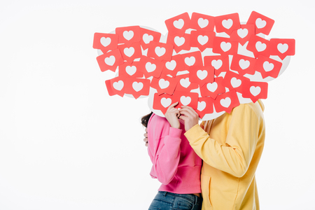 Photo for young man and woman in bright hoodies hiding behind faces behind red paper cut cards with heart symbols isolated on white - Royalty Free Image