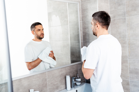 Photo pour Handsome man wiping hands with towel in bathroom during morning - image libre de droit