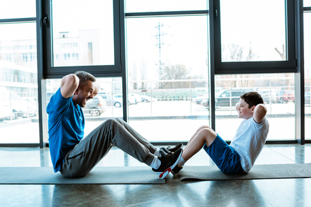 Photo pour Father and son doing sit up exercise on fitness mats at gym - image libre de droit