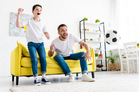 Photo pour Excited father and son cheering while watching sports match in Living Room - image libre de droit