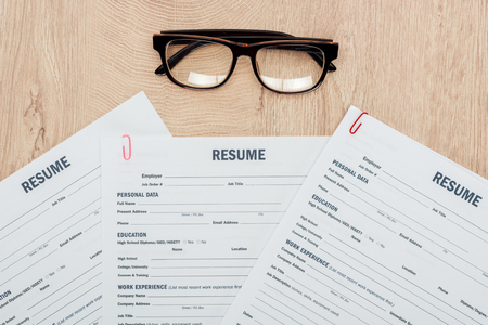 Photo for Top view of print resume templates and glasses on wooden table - Royalty Free Image