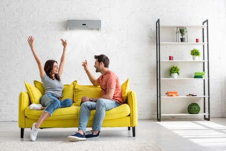 Foto de Happy man and woman talking while sitting on yellow sofa under air conditioner at home - Imagen libre de derechos