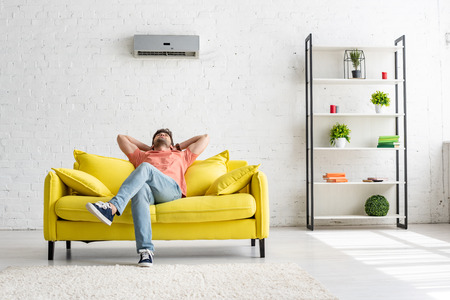 Photo pour Young man sitting on yellow sofa under air conditioner in spacious apartment - image libre de droit