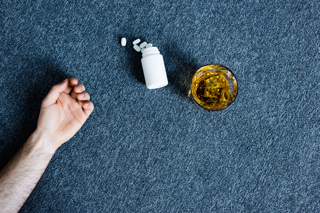Foto de Cropped view of man lying on grey floor near glass of whiskey and container with pills - Imagen libre de derechos