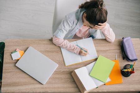 Foto de overhead view of schoolchild doing homework while sitting at wooden desk near book, notebooks, laptop and pencil case - Imagen libre de derechos