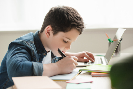 Photo pour adorable attentive boy writing in notebook and using laptop while doing homework - image libre de droit