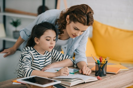 Photo pour attentive mother helping adorable daughter doing schoolwork at home - image libre de droit
