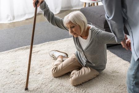 Foto de cropped view of man helping sick senior mother with cane fallen on floor - Imagen libre de derechos
