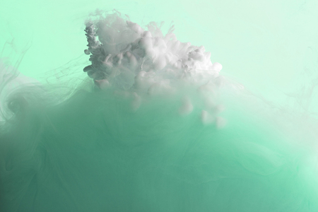 Photo for Close up view of green and white acrylic paint mixing in water - Royalty Free Image