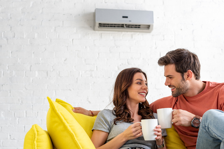 Photo pour happy couple with cups sitting on sofa under air conditioner at home - image libre de droit