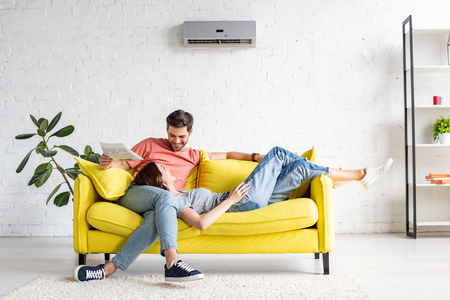 Foto de happy man with smiling girlfriend relaxing on yellow sofa under air conditioner at home - Imagen libre de derechos