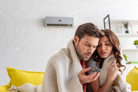 Photo pour handsome man holding remote control while warming under blanket with pretty girlfriend at home - image libre de droit