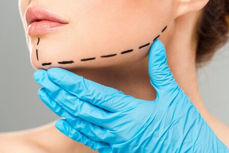 Photo pour Cropped view of plastic surgeon touching face of woman with marked face isolated on grey background - image libre de droit