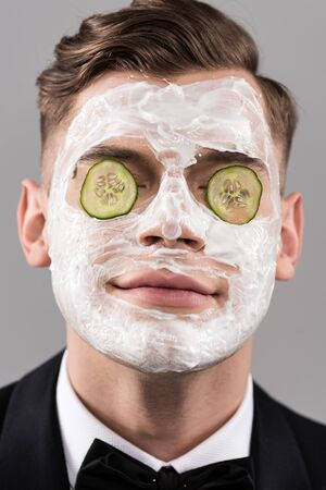 Photo pour Portrait of young man in formal wear with cucumber facial mask isolated on grey background - image libre de droit