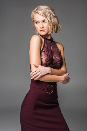 Foto de Beautiful stylish blonde girl in burgundy clothes posing isolated on grey background - Imagen libre de derechos