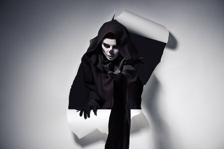 Foto de Woman in death costume with outstretched hand getting out of hole in paper - Imagen libre de derechos